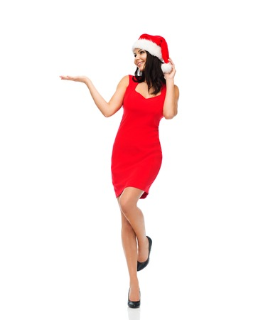 christmas hat: people, holidays, christmas and advertisement concept - beautiful sexy woman in santa hat and red dress showing something on empty hands Stock Photo