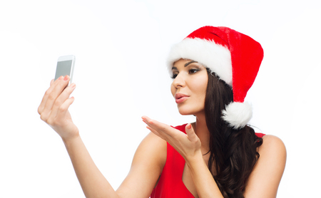 santa hat: people, holidays, christmas and technology concept - beautiful sexy woman in red santa hat taking selfie picture by smartphone and sending blow kiss to camera