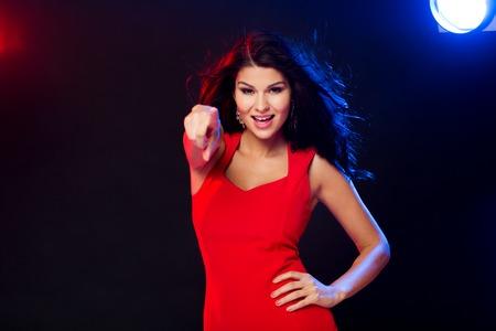 femme brune sexy: les gens, vacances, vie nocturne, le geste et concept de loisirs - belle femme sexy en robe rouge pointant le doigt sur vous � la discoth�que en discoth�que