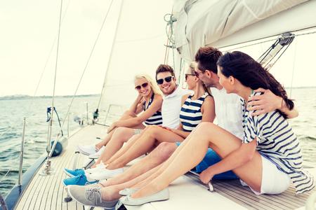 휴가, 여행, 바다, 우정과 사람들 개념 - 요트 갑판에 앉아 웃는 친구 스톡 콘텐츠