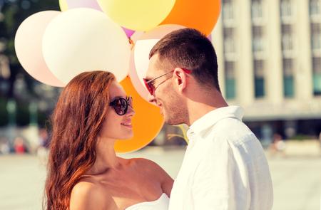 donna innamorata: amore, matrimonio, l'estate, la datazione e la gente concept - sorridente coppia che indossa occhiali da sole con palloncini abbracciare in città
