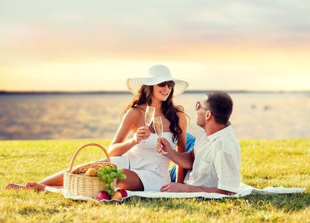 愛、出会い、人との休日のコンセプト - シーサイド夕日を背景にピクニックにシャンパンを飲んで幸せなカップル