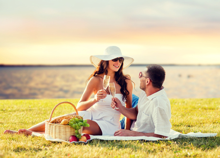 seaside: love, dating, people and holidays concept - happy couple drinking champagne on picnic over seaside sunset background Stock Photo