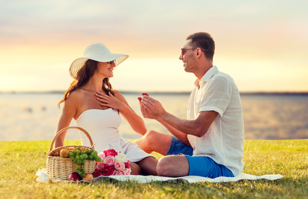 proposing: love, dating, people, proposal and holidays concept - smiling young man giving small red gift box with wedding ring to his girlfriend on picnic over seaside sunset background