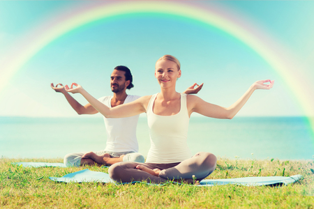 chakra: sport, fitness, yoga and people concept - smiling couple meditating and sitting on mats over sea and rainbow in blue sky background Stock Photo