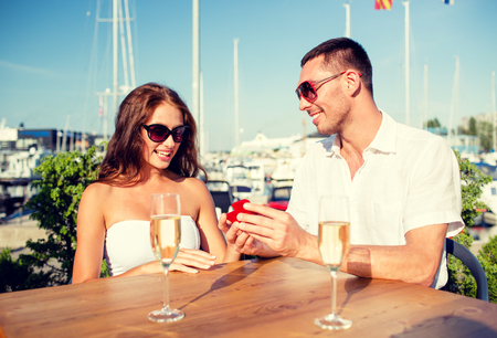 champagne glasses: love, dating, people and holidays concept - smiling couple wearing sunglasses with champagne and small red gift box looking to each other at cafe