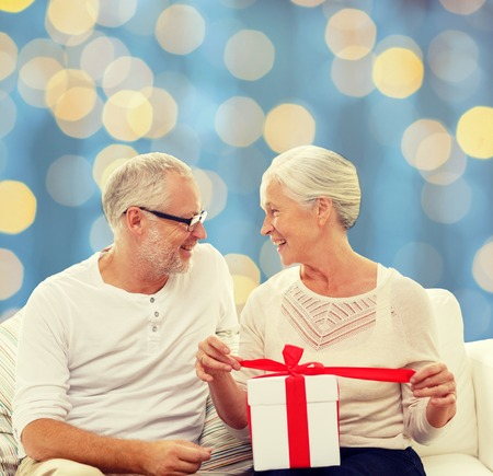 winter holiday: family, holidays, christmas, age and people concept - happy senior couple with gift box over blue lights background