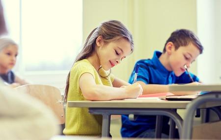 salle de classe: l'éducation, l'école primaire, l'apprentissage et les gens notion - groupe d'enfants de l'école avec des stylos et des cahiers d'écriture test classe
