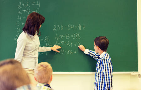 teacher student: education, elementary school, learning, math and people concept - close up of little schoolboy with teacher writing on chalk board and solving task in classroom