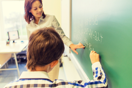 math: education, elementary school, learning, math and people concept - close up of little schoolboy with teacher writing on chalk board and solving task in classroom