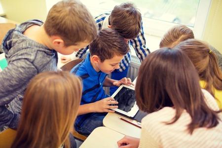 salle de classe: l'éducation, l'école primaire, l'apprentissage, la technologie et les gens notion - groupe d'enfants de l'école avec l'ordinateur tablette pc en se amusant sur la rupture dans la classe