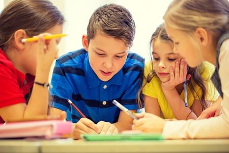 persona escribiendo: educación, escuela primaria, el aprendizaje y el concepto de la gente - grupo de niños de la escuela con lápices y papeles de escritura en el aula Foto de archivo