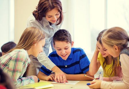 preteen: education, elementary school, learning and people concept - teacher helping school kids writing test in classroom