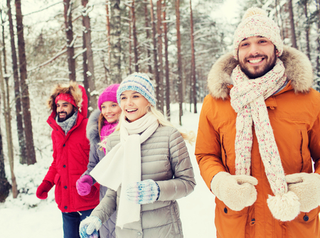 사랑, 관계, 계절, 우정과 사람들 개념 - 남자와 여자 미소의 그룹은 겨울 숲에서 실행