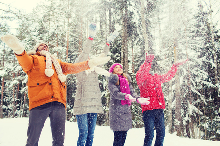 snow forest: love, relationship, season, friendship and people concept - group of smiling men and women having fun and playing with snow in winter forest Stock Photo