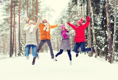 personas saltando: el ocio, la estación, la amistad y el concepto de la gente - grupo de sonrientes hombres y mujeres que se divierten y saltar en el bosque de invierno