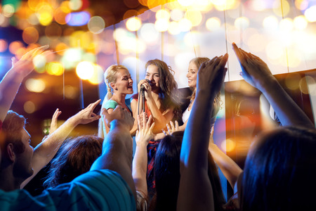 party, holidays, celebration, nightlife and people concept - happy young women singing karaoke in night club behind crowd of music fan Foto de archivo