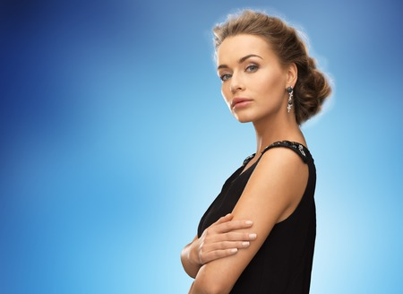 hollywood christmas: people, holidays and glamour concept - beautiful woman wearing earrings over blue background