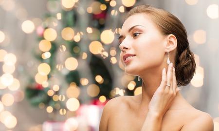 아름다움, 럭셔리, 사람들, 휴일 및 보석 개념 - 크리스마스 조명 배경 위에 다이아몬드 귀걸이와 아름 다운 여자