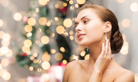 in jewelry: beauty, luxury, people, holidays and jewelry concept - beautiful woman with diamond earrings over christmas lights background