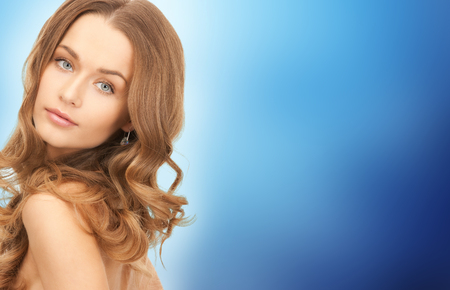soft skin: people, beauty, hair and skin care concept - beautiful woman with curly hairstyle over blue background