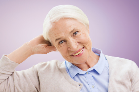 senior women: age and people concept - happy smiling senior woman over violet background Stock Photo