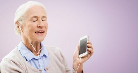 personas escuchando: la tecnología, la edad y las personas concepto - mujer mayor feliz con el teléfono inteligente y los auriculares escucha la música sobre el fondo violeta Foto de archivo