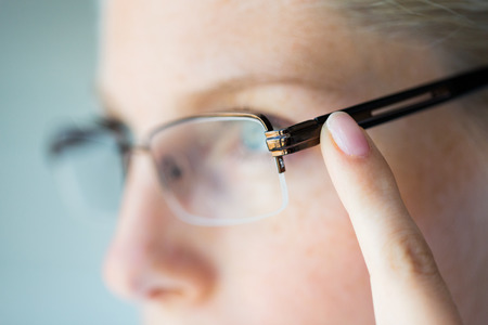 myopia: business, vision and people concept - close up of woman in eyeglasses pointing finger to earpiece