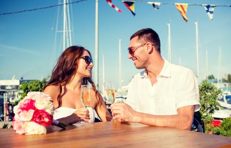 aniversario de boda: amor, el fechar, personas y concepto de vacaciones - sonriente pareja con gafas de sol bebiendo champán y mirando el uno al otro en el café