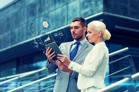 zaken, partnerschap, technologie en mensen concept - zakenman en zakenvrouw werken met tablet pc computer grafieken op virtuele schermen op straat in de stad Stockfoto
