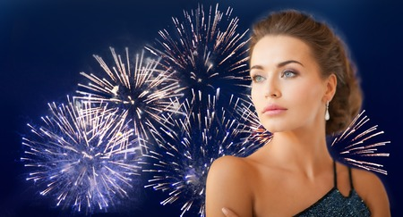 style woman: people, holidays and glamour concept - beautiful woman wearing earrings over firework on dark blue background