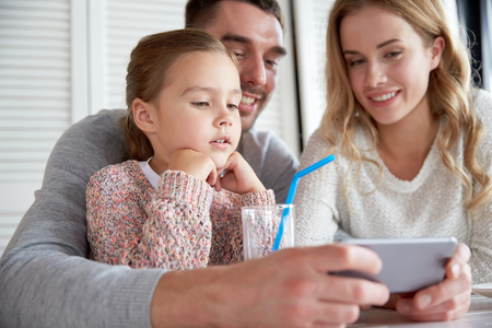 family, parenthood, technology and people concept - happy mother, father and little girl with smartphone having dinner at restaurant