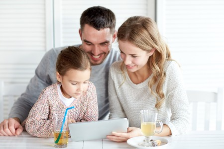 family, parenthood, technology and people concept - happy mother, father and little girl with tablet pc computer having dinner at restaurant Stock Photo - 48790162