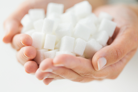 food, junk-food, diabetes and unhealthy eating concept - close up of white lump sugar in woman hands Stok Fotoğraf - 48790163