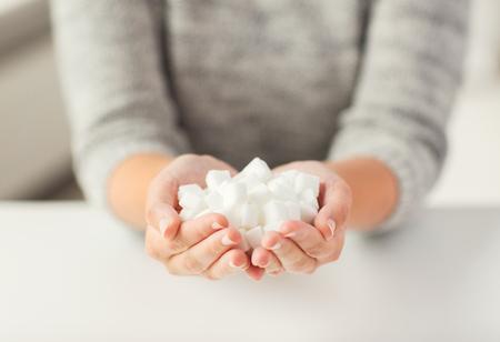 食品、ジャンク フード、糖尿病および不健康な食事の概念 - は、女性の手で白い角砂糖のクローズ アップ 写真素材