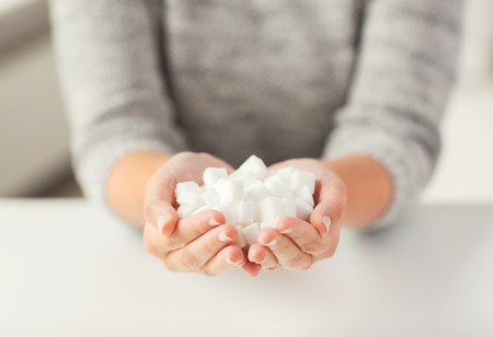 white sugar: food, junk-food, diabetes and unhealthy eating concept - close up of white lump sugar in woman hands