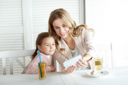 mum: family, parenthood, technology and people concept - happy mother and little girl having dinner and taking selfie by smartphone at restaurant