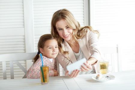 mama e hija: la familia, la paternidad, la tecnolog�a y la gente conceptuales - feliz madre y la ni�a cenando y tomando selfie por tel�fono inteligente en el restaurante