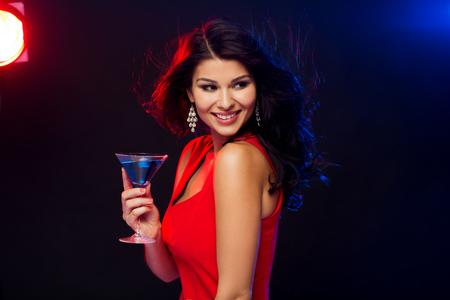 mujer elegante: gente, días de fiesta, fiesta, el alcohol y el concepto de ocio - mujer atractiva en vestido rojo con vaso de cóctel en el club nocturno