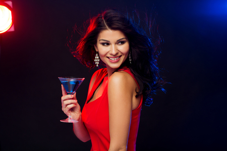 people, holidays, party, alcohol and leisure concept - beautiful sexy woman in red dress with cocktail glass at night club Imagens