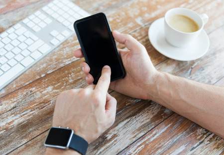smart: business, technology and people concept - close up of male hand holding smart phone and wearing watch with coffee and keyboard at wooden table Stock Photo