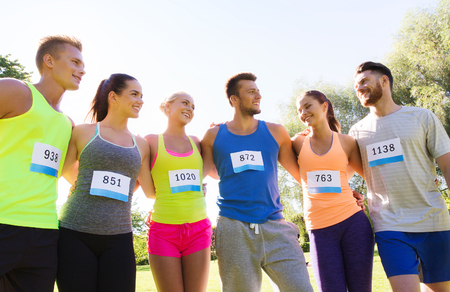 summer sport: fitness, sport, marathon, friendship and healthy lifestyle concept - group of happy teenage friends or sportsmen couple with racing badge numbers outdoors Stock Photo