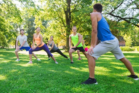 boot camp: fitness, sport, friendship and healthy lifestyle concept - group of happy teenage friends or sportsmen exercising and doing lunge at boot camp Stock Photo