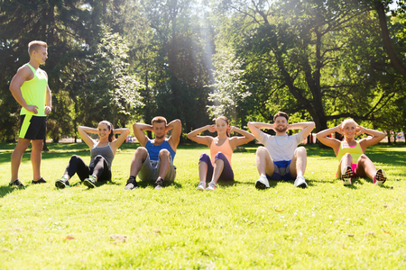 loss: fitness, sport, friendship and healthy lifestyle concept - group of happy teenage friends or sportsmen exercising and doing sit-ups at boot camp