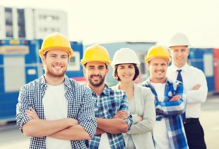 mujer trabajadora: negocio, construcci�n, trabajo en equipo y concepto de la gente - grupo de sonrientes constructores de cascos al aire libre Foto de archivo