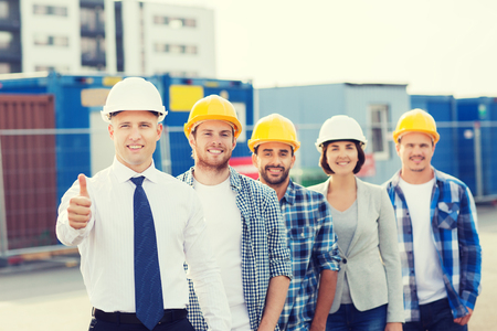 Industrial workers: business, building, teamwork, gesture and people concept - group of smiling builders in hardhats showing thumbs up outdoors