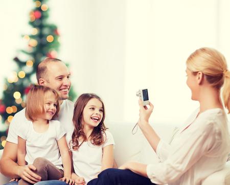 mom dad: familia, días de fiesta, la tecnología y la gente - sonriendo madre, padre y niñas con la cámara sobre el salón y el fondo del árbol de navidad