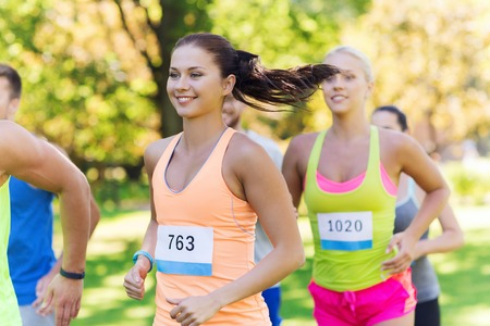 race: fitness, sport, friendship, race and healthy lifestyle concept - group of happy teenage friends or sportsmen running marathon with badge numbers outdoors