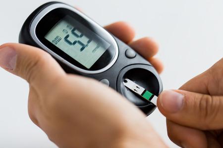 geneeskunde, diabetes, glycemie, de gezondheidszorg en de mensen concept - close-up van de mens de controle bloedsuikerspiegel door glucometer en test streep thuis Stockfoto
