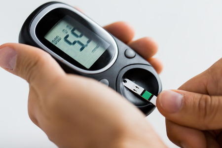 glucometer: medicine, diabetes, glycemia, health care and people concept - close up of man checking blood sugar level by glucometer and test stripe at home